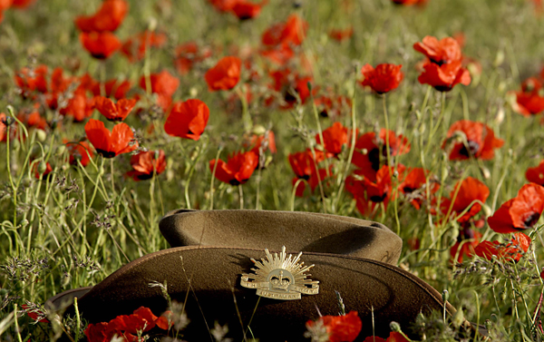 Photographer: Leading Aircraftman Rodney Welch  Caption: An Aussie Slouch hat surrounded by poppy flowers in Afghanistan.  The poppy is a significant symbol in military traditions dating back to the First World War. ANZAC day for the Australian Reconstruction Task Force will be marked by fields of wild poppies, similar to those experienced in the European and African Campaigns of 1914-18 and 1939-45.   Deep Caption: Australia has deployed an ADF Reconstruction Task Force (RTF), consisting of a combined arms team, to the Uruzgan Province in Southern Afghanistan as part of Operation Slipper. The RTF is in partnership with the Netherlands Provincial Reconstruction Team (PRT) and forms part of the NATO- led International Security Assistance Force.  The RTF has a clearly defined role to work on reconstruction, improvement of provincial infrastructure and community based projects. The RTF also provides trade training to the local population and military engineering training to the Afghan National Army. This type of assistance is designed to benefit the people of  Uruzgan Province well into the future and form building blocks of a stable  and prosperous community.  The RTF contains around 370 ADF personnel from predominately Queensland based units. It includes elements to provide command, security, engineering, and administrative support and is equipped with Bushmaster Infantry Mobility Vehicles (IMV), Australian Light Armoured Vehicles (ASLAVs) and armoured engineer plant equipment.  Australia's contribution to ISAF is an important component of the Australian Government's commitment to assist Afghanistan achieve a stable  and secure future.